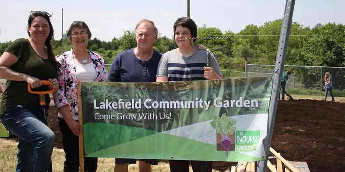 People holding banner. Text reads: Nourish Lakefield Community Garden: 'Come Grow With Us!